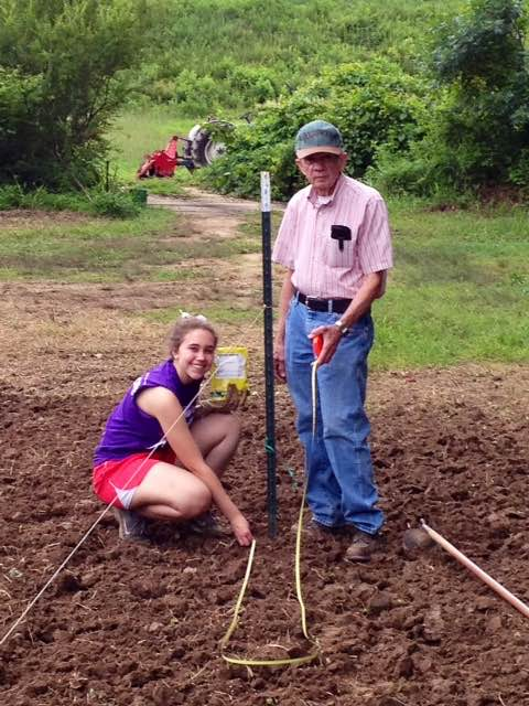Breann Pritchett with her grandfather Marving Pritchett planting pumpkins