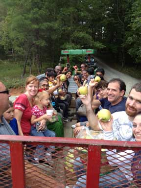 U-Pick wagon rides families back at the Apple Barn after a picking apples in the